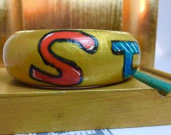 Yellow multi colored wood bangle with a graffiti style affirmation.
