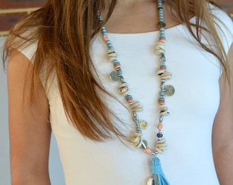 Pretty blue suede tassel boho beaded necklace with cowrie shells, chain and small coins.