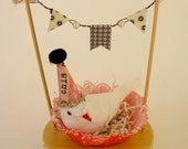decorative cake topper with a nested bird ready to celebrate!