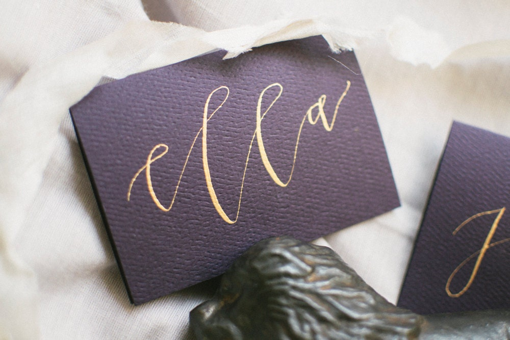 Modern calligraphy aubergine purple place cards with gold ink