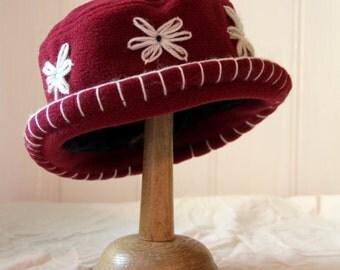 A burgundy daisy fleece cloche hat
