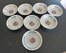 Eight Winterling Bavarian Porcelain dessert bowls with gold decoration and printed Fragonard paintings.