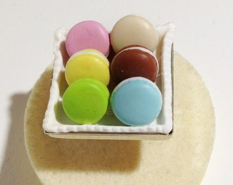Half a dozen colorful macarons on a square silver plated ring