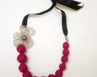 Lovely and original handmade colorful textile necklace with black ribbons.