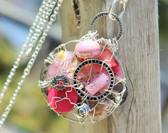 Pink Round Whimsical, MUSKOKA STONE wire wrapped pendant is made with sterling silver wire, glass, resin, shell, ceramic and pewter beads.
