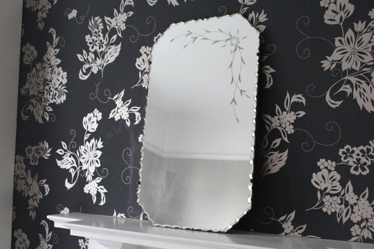 Vintage frameless mirror with decorative edge and flower
