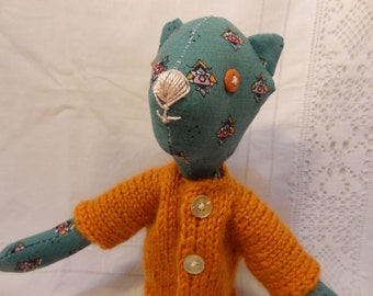 Rag doll, security blanket, small green articulated cat with small flowers