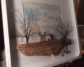 Secret Cove , the title for this framed piece of work , driftwood , sea trees, harbour cottages ,anchor, sailing boat , sea buoys, harbour