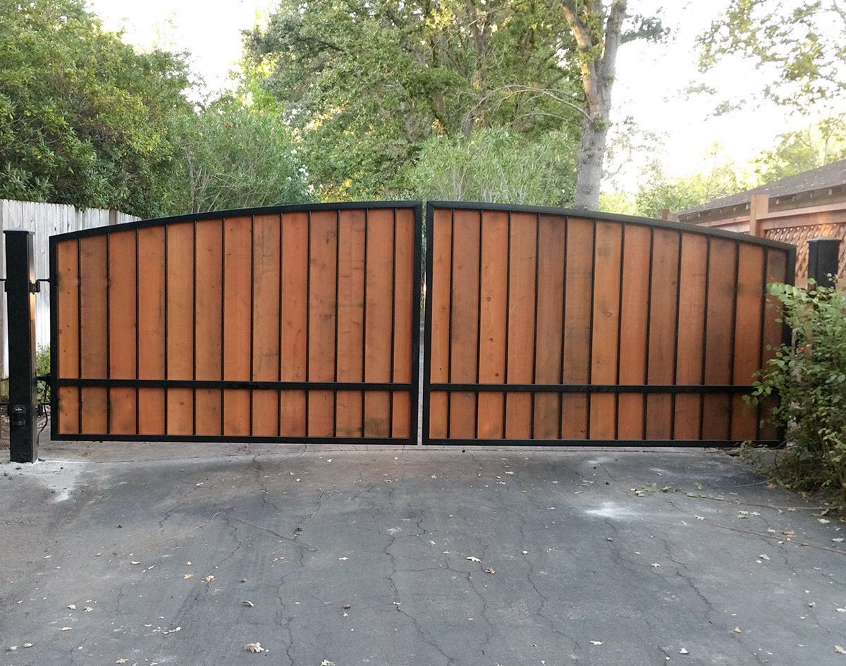 Dual wrought iron and wood driveway gate with posts hinges
