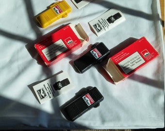 3 Vintage 1992 Marlboro Adventure Team Butane Lighters.  2 are black while 1 is yellow.  All are new in the box.
