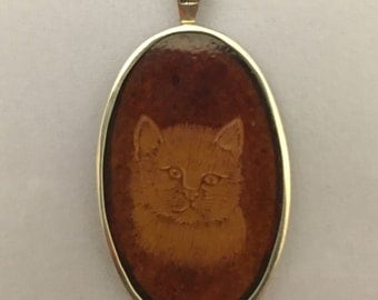 Pendant, Etched cat head in amber. (Reversed etching)