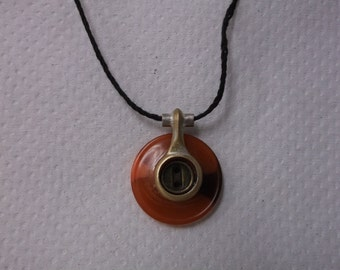This is a necklace made from a vintage clarinet key and a button.