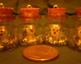 Kodamas or Tree Spirits that glow in the dark in a bottle pendant.
