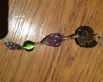 Ammonite fossol, czech glass bead and guinea fowl feather. Lovely combination lf fowl, fossil & crystal