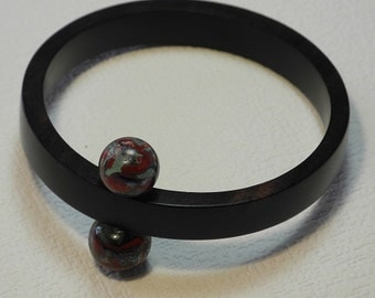 Round bracelet in ebony, with 2 glass beads face-to-face, Garnet filaments and deep purple on bottom transparent steel, surface patinated
