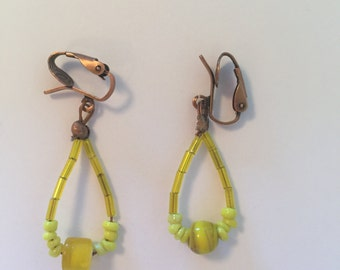 Yellow glass beads loop up to bronze ear clips. Handmade, one of a kind earrings.