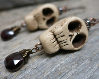 Muerte earrings ... antiqued handcrafted polymer skulls / wire wrapped garnet / hand forged earwires