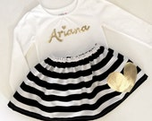 Gold cursive name OUTFIT in black and white stripe with gold accents.. girls clothing