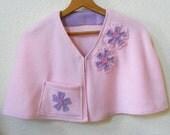 Woman's pale pink appliquéd fleece cape, capelet or bed jacket.