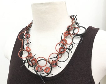 ALL RUBBER-three strand necklace-black/red 0 rings of various sizes. Light weight-modern.