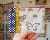 Scalloped butterfly pouch