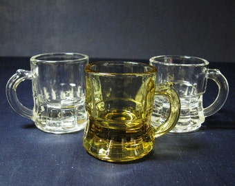 Collection of Three Miniature Mugs, Two Crystal Clear Manufactured by Federal Glass Company, One Unmarked Amber Glass