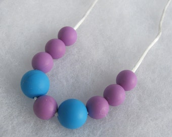 Silicone Teething Necklace. Purple and Blue. Silk cord. Snap safety closure.