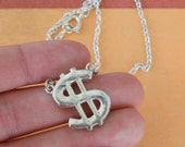 1970s 1980s DOLLAR Sign Necklace.NOS. silver. new old stock. retro. costume jewelry. 1980s. necklaces. charms. gangsta. wall street. money.