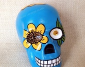 Hand painted ceramic skull by Susie Carranza. Turquoise blue with orange and yellow sunflower. Flower and gem eyes.