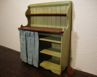 dollhouse miniature country shabby chic green . with shelves in natural wood. in Tuscan style.