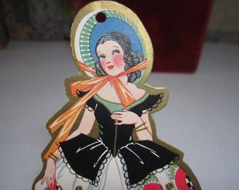 Art deco 1930's gold gilded die cut bridge tally card pretty lady w/ ringlets wears a large bonnet and colorful deco patterned flower dress
