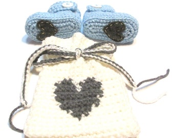 Baby boy booties in a gift bag with  heart.  Gender reveal baby boy, pregnancy reveal, boy baby shower gift idea.  Baby blue and grey.