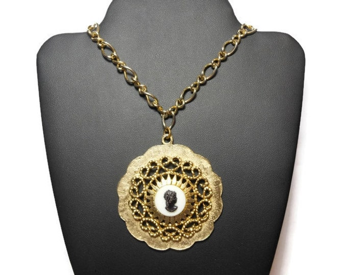 FREE SHIPPING Cameo pendant, black on white celluloid centered on a gold starburst frame gold filigree open scroll work gold ruffled edging