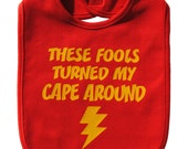 These fools turned my cape around baby bib infant toddler boy / girl / unisex funny superhero shower gift -  red and yellow