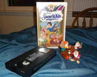 """Disney movie VHS video of """"Snow White"""", with three character figures including some of the dwarfs"""