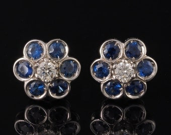 A charming pair of natural sapphire and diamond daisy stud earrings