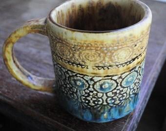 A beautiful brown and glossy green, lace imprint handmade ceramic mug