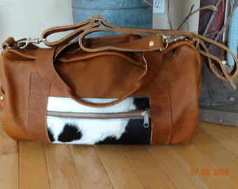Leather and black/white cowhide duffel bag