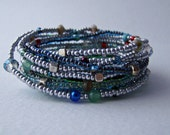 Handmade extra long bracelet/necklace with silver, blue, green seed beads and various colourful beads on an elastic jewellery cord