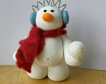 Snowman with earmuffs holding snowball ornament