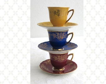 3 demitasse cups and saucers, yellow, blue, burgundy with gilt edges and gilt floral bouquets, Czechoslovakia, RGK, 1928 - 1938