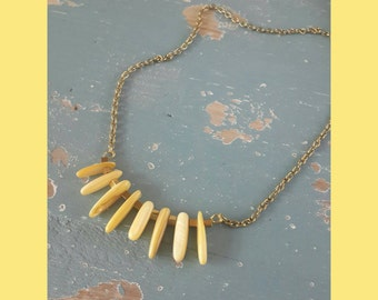 Yellow shell necklace with Hematite cube beads, on a Brass chain