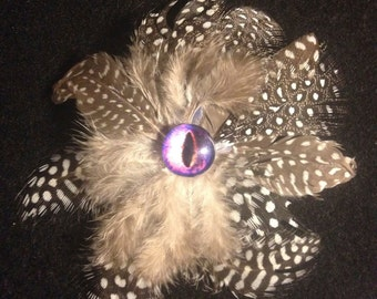 Brooch with feathers and one eye ...