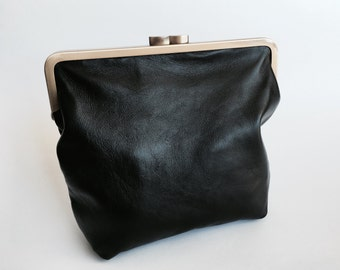 Small leather clutch with an antique brass clasp and natural linen lining