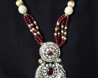 Necklace and earing set made of ruby colour stones  along with 1 complimentary necklace and earrings