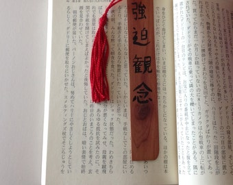 Obsession in Japanese calligraphy on a wooden bookmark with a red tassel