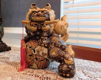 Large porcelain foo dog shi on ball sword with red tassel in mouth lion dog chocolate and gold from China 1970s guardian lion