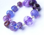 Handmade lampwork glass bead set of 12 mainly purple renegade lampwork orphans