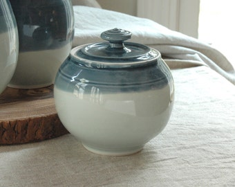 Small handmade porcelain lidded jar in deep blue and light green