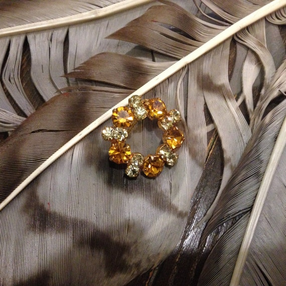 Gold colored vintage brooch, with amber sparkly and white rhinestones